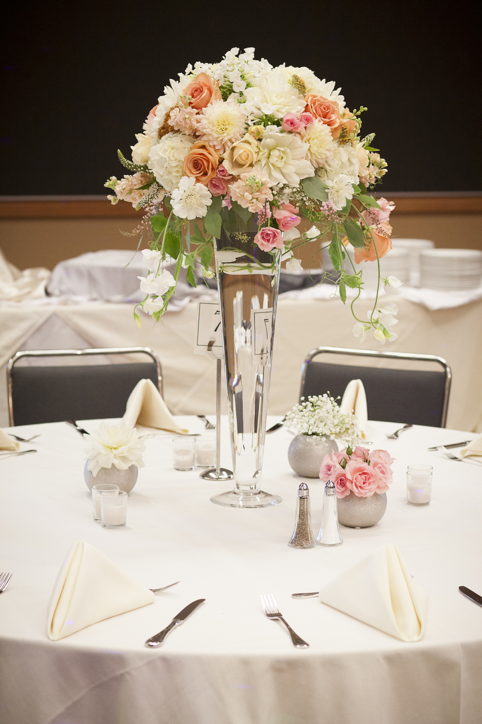 wedding centerpiece with blush and peach roses, white hydrangea and sweet peas