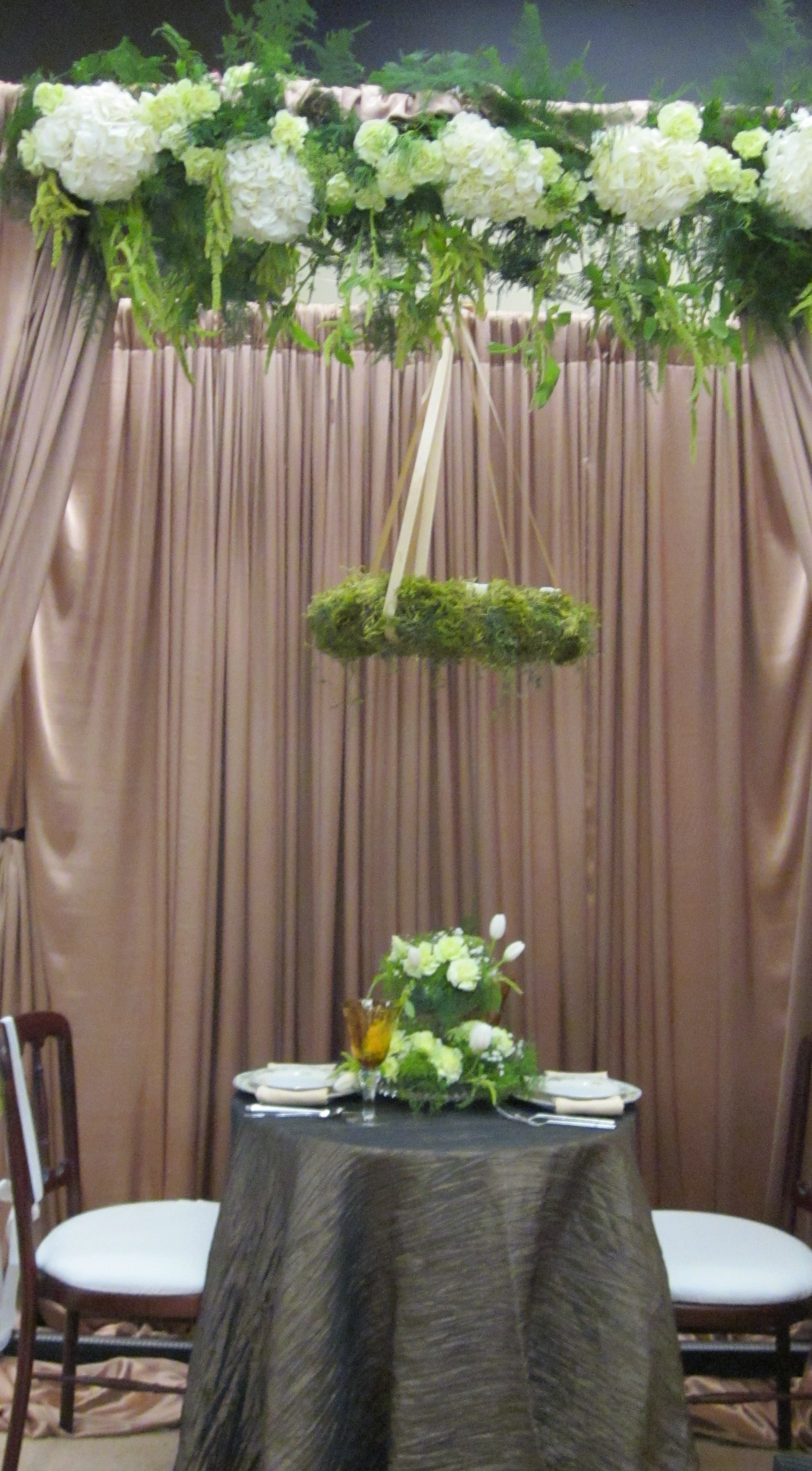 image of woodland-theme wedding table with moss chandelier and flower garland