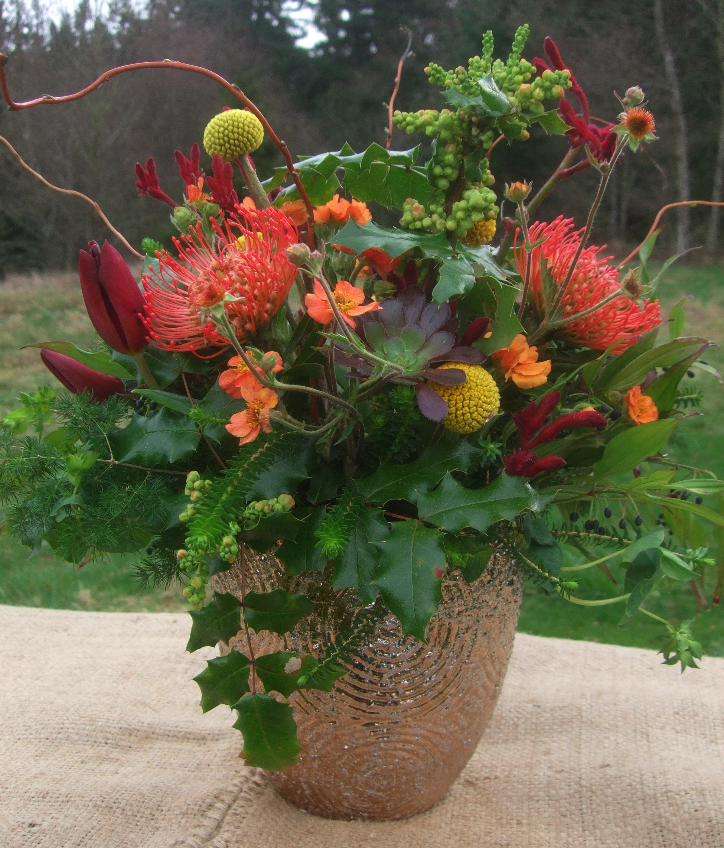 image of hot colored bouquet in a mettallic bronze vase