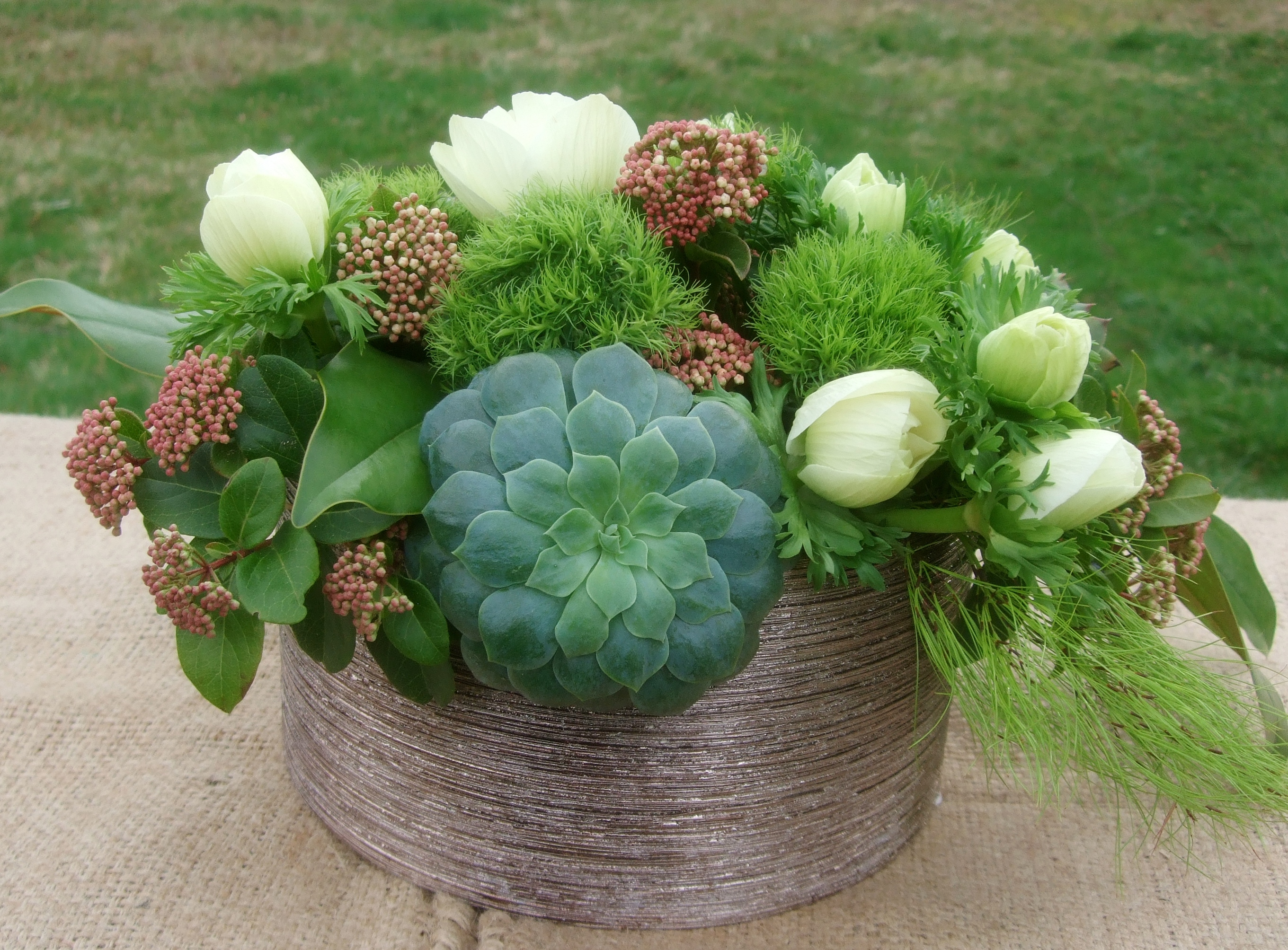 image of centerpiece with succulents and moss and white anenome