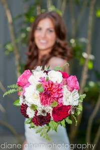 bride holding red and pink bridal bouquet