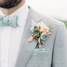 grey and blush boutonniere with sedums and rose